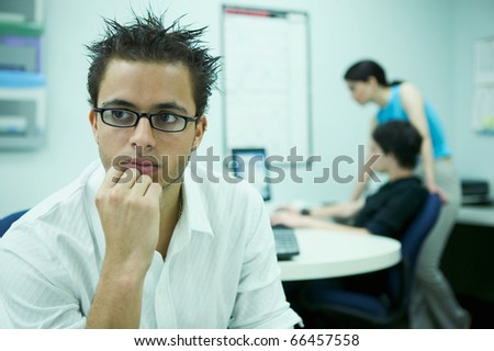 Young man sitting in an office with people working behind - stock photo