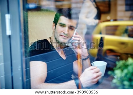 Young man sitting in cafeteria, drinking coffee and talking on phone. Photographed through window. - stock photo