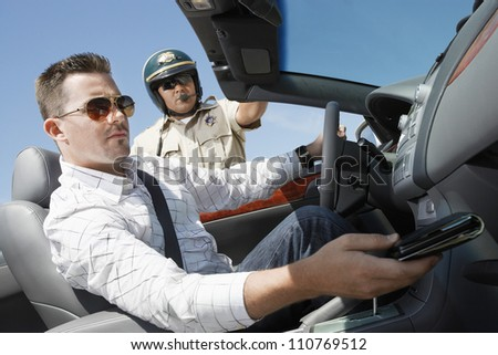 Young man sitting in car with wallet - stock photo