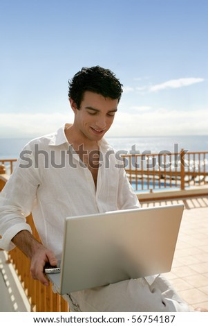 Young man sitting in front of a laptop computer on a terrace