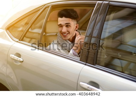 young man sitting in the back seat, looking out the windows winking and showing raised thumb - stock photo