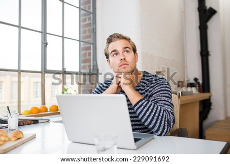 Young man sitting in the kitchen area of his apartment thinking at his laptop looking up thoughtfully into the air with his chin on his hands - stock photo
