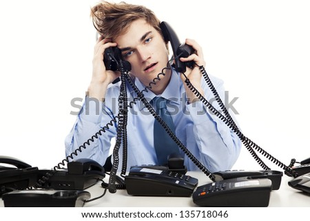 Young man sitting in the office and answering several phones at the same time - stock photo