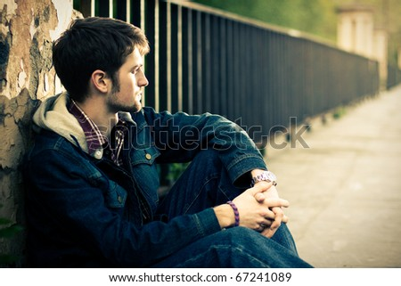 Young man sitting near the fence in sunlight - stock photo