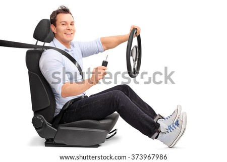 Young man sitting on a car seat and holding a steering wheel and a car key isolated on white background - stock photo