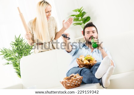 Young man sitting on a couch, holding a bottle of beer in one hand, remote control in the other hand, while behind him stands a young woman with a rolling pin in hand with an angry expression. - stock photo