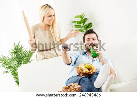 Young man sitting on a couch, while behind him stands a young woman with a rolling pin in hand with an angry expression. - stock photo