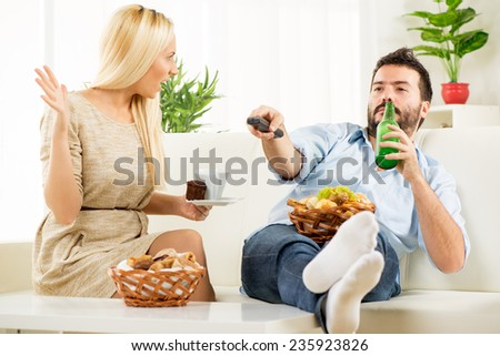 Young man sitting on a couch with his feet on the table, holding a bottle of beer in one hand, remote control in the other hand, while sitting next to him pretty blonde woman shouting at him. - stock photo