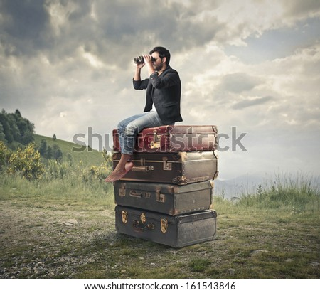 young man sitting on a pile of vintage suitcases looking with binoculars the panorama - stock photo