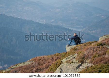 Young man sitting on a rock and looking to a valley below - stock photo