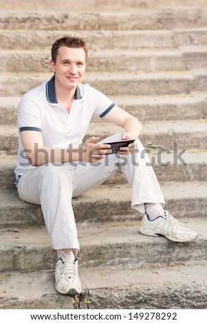 Young man sitting on a stairs with tablet pc outdoor - stock photo