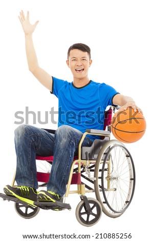 young man sitting on a wheelchair and holding a basketball - stock photo