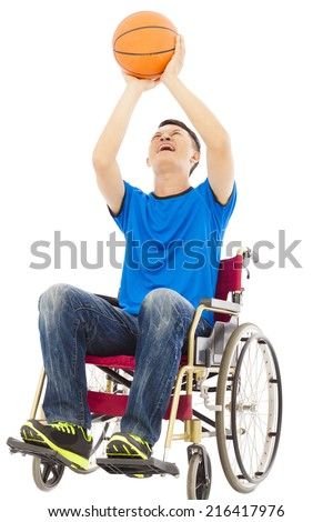 young man sitting on a wheelchair and holding a basketball over white background - stock photo
