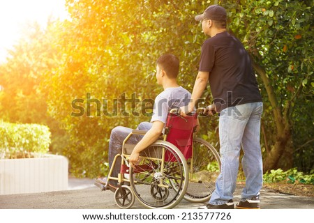 young man sitting on a wheelchair with his brother - stock photo
