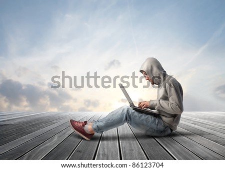 Young man sitting on a wooden floor and using a laptop - stock photo
