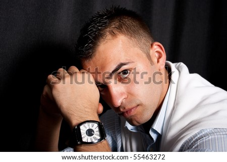 Young man sitting on an armchair - stock photo