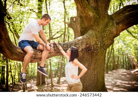 Young man sitting on big tree invites his girlfriend standing bellow - stock photo