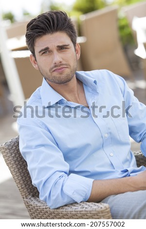 Young man sitting on chair at outdoors cafe - stock photo