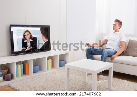 Young Man Sitting On Couch And Watching Movie At Home - stock photo