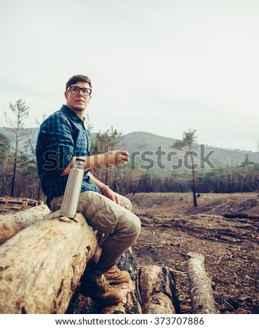 Young man sitting on fallen tree trunk and drinking tea from thermos. Handsome man resting outdoor - stock photo