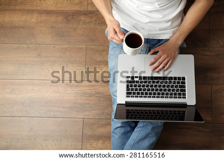 Young man sitting on floor with laptop and cup of coffee in room - stock photo