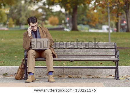 Young Man Sitting On Park Bench, Looking Bored With His Work - stock photo