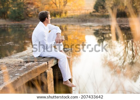 young man sitting on pier with wine and enjoying sunset view by the lake - stock photo