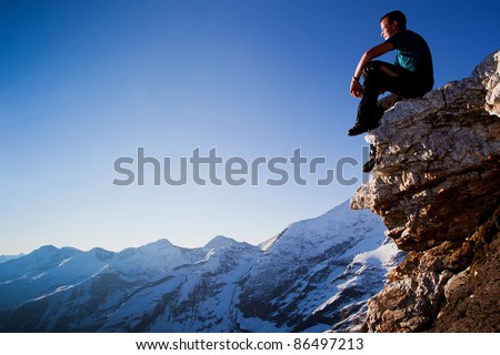 Young man sitting on rock above mountain range - stock photo