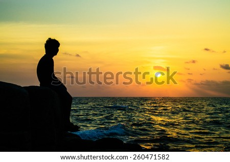 Young man sitting on rock overlooking ocean - stock photo