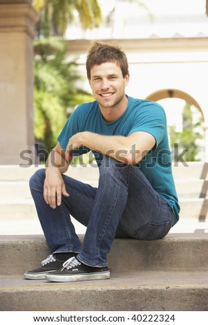 Young Man Sitting On Steps Of Building