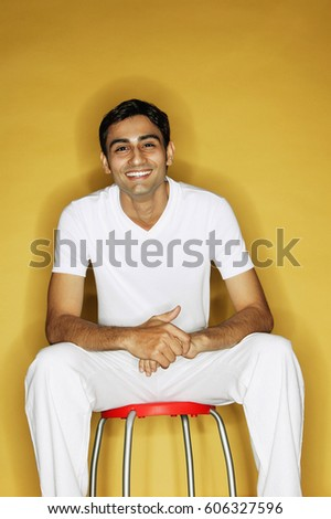 Young man sitting on stool, looking at camera