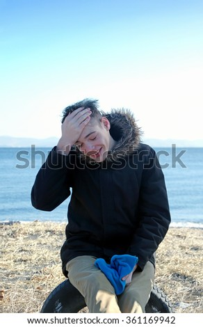 Young man sitting on the beach in winter clings to his forehead surprised and laughs - stock photo