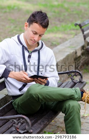 Young man sitting on the bench and using mobile device.