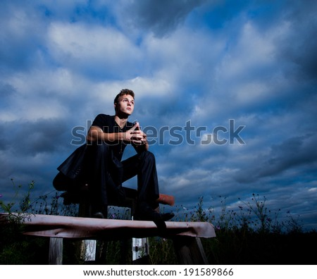 Young man sitting on the bench in the middle of the field. Dark blue sky clouds background - stock photo