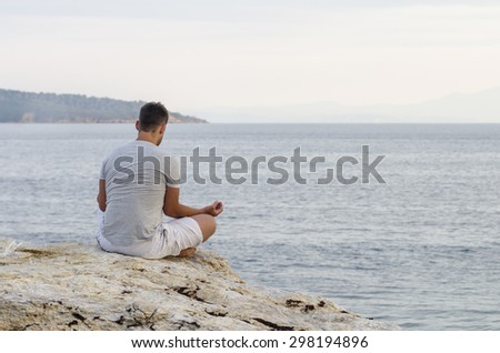 Young man sitting on the coast and meditating - stock photo