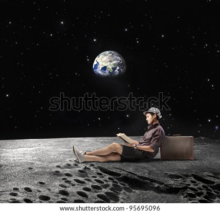 "Young man sitting on the Moon and reading a book with Earth in the background ""Elements of this image furnished by NASA"" - stock photo"