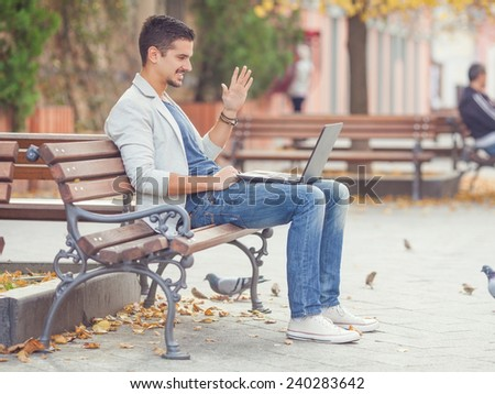 Young man sitting on the park bench and video-chatting on his laptop - stock photo