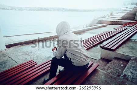 young man sitting on the promenade on a cloudy day - stock photo