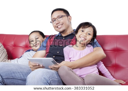 Young man sitting on the sofa with his children while holding a digital tablet and smiling at the camera