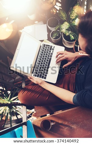 Young man sitting On the stairs in a studio and working on his laptop. Blank screen - stock photo