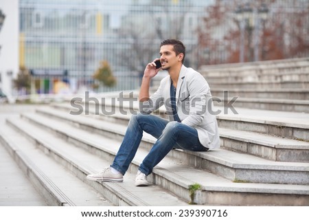Young man sitting on the steps talking on the mobile phone - stock photo