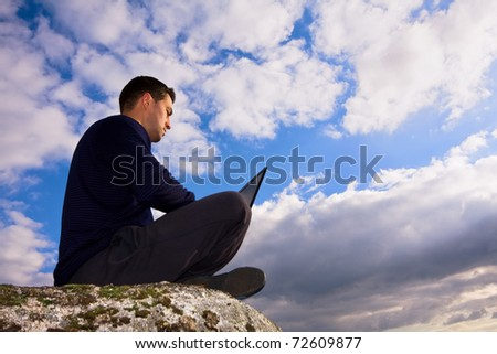 Young man sitting on the top of mountain working with laptop - stock photo