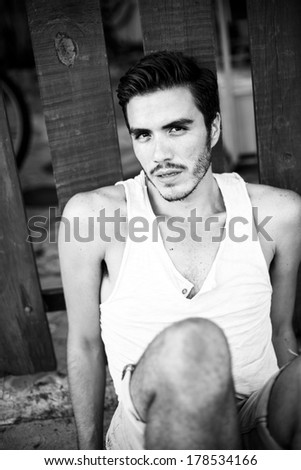 Young man sitting outdoors in summer wear staring serious at the camera in a urban background