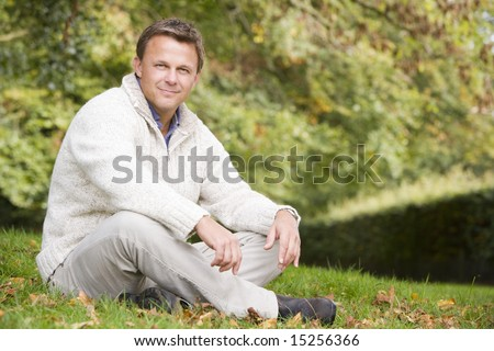 Young man sitting outside on grass in autumn landscape - stock photo