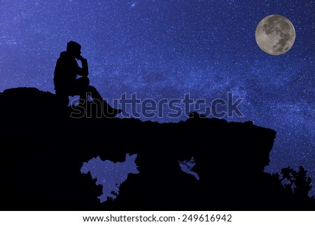 Young man sitting under the stars - stock photo