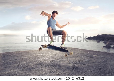 Young man skateboarding on a beach - stock photo