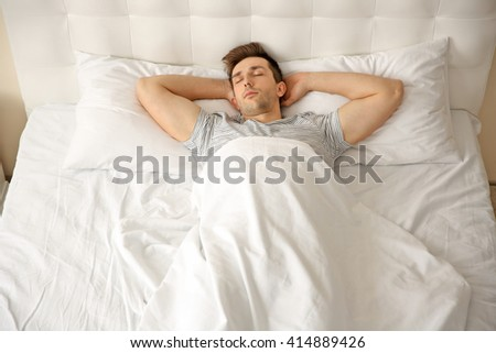 Young man sleeping alone in white big bed
