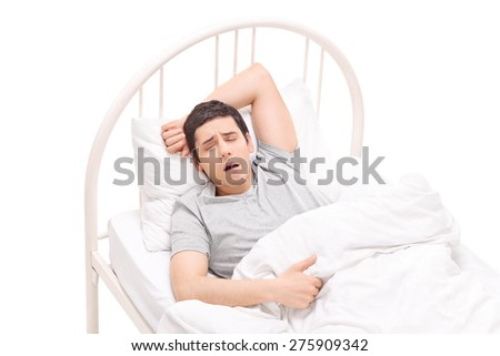 Young man sleeping in a bed and having nightmares isolated on white background - stock photo