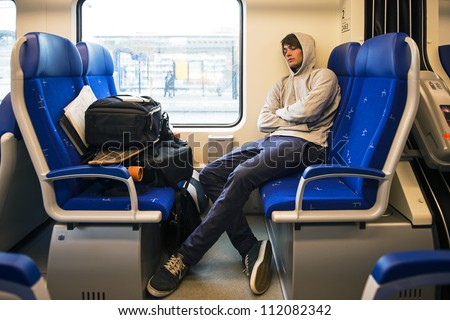 Young Man Sleeping In Train With Luggage - stock photo