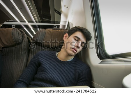 Young man sleeping while traveling on a train sitting in a passenger coach with his head resting on his hand and eyes closed - stock photo
